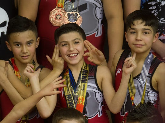 Bryson Valdez, left, Zander Bahri and Mark Martinez have fun during a team photo session on Wednesday at Stout Wrestling Academy in Farmington