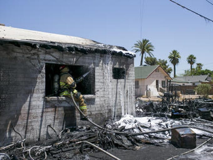 Firefighters work to extinguish a structure fire near