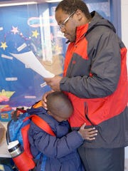 Kindergarten student Caleb Chinyadza hugs his dad, Tanyanyiwa Chinyadza, who is reading materials for class.