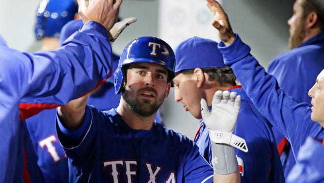 Texas Rangers' Brett Nicholas is greeted in the dugout after he scored a run in the seventh inning of a baseball game against the Seattle Mariners, Monday, April 11, 2016, in Seattle.