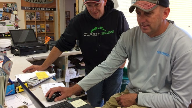 The owner of Howie's Tackle, Mike Richard, checks his computer for Bassmaster Angler of the Year updates while Nick Nault watches on the first day of the tournament, which is based in Sturgeon Bay.