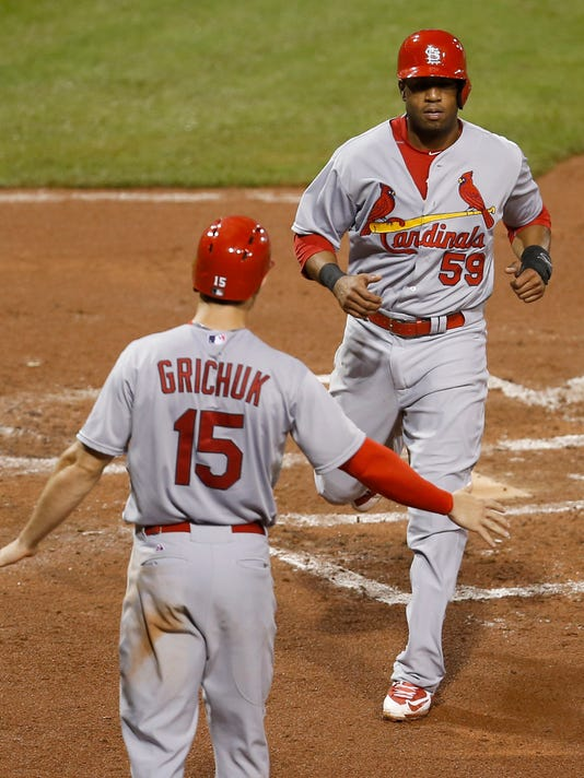St. Louis Cardinals' Randal Grichuk (15) greets Xavier Scruggs (59) after they both scored on a bases-loaded hit by Matt Carpenter during the fifth inning of a baseball game against the Pittsburgh Pirates, Thursday, July 9, 2015, in Pittsburgh. (AP Photo/Keith Srakocic)