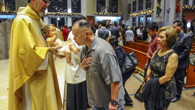 In this file photo, Monsignor David Quitugua, left, presents a statue of the baby Jesus to a parishioner to kiss after the midnight Christmas Mass at the Dulce Nombre de Maria Cathedral-Basilica in Hagatna on Dec. 25, 2014.