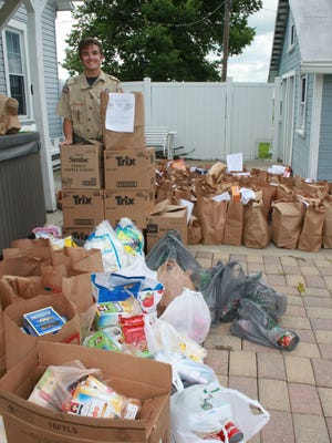 Kenneth Fernandez, of Galion, stands with the food he's collected for his Eagle Scout Project. The food is for those in need.