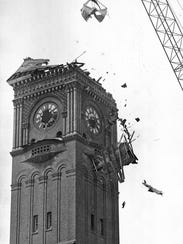A crane rips away the top of the clock tower at the