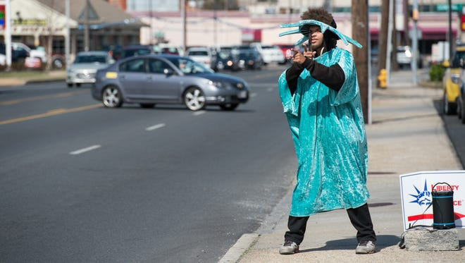 Johan Galon, 18, of Salisbury, dances along Route 13 to attract attention to an income tax business Monday, March 13, 2017.