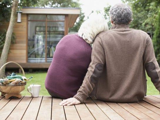 Older Couple Sitting On Wood Deck