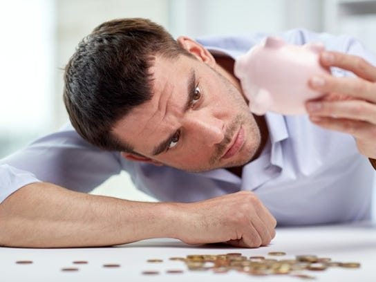 Man Emptying Piggy Bank Of Coins Getty