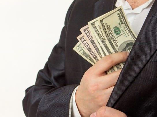Businessman Putting Money In Jacket Pocket Dividend Getty