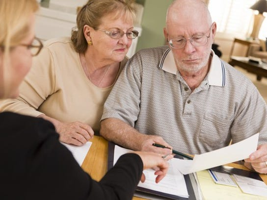 Senior Couple Discussing Paperwork With Advisor Getty