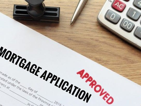 """corner of a mortgage application, stamped """"approved"""" in red"""