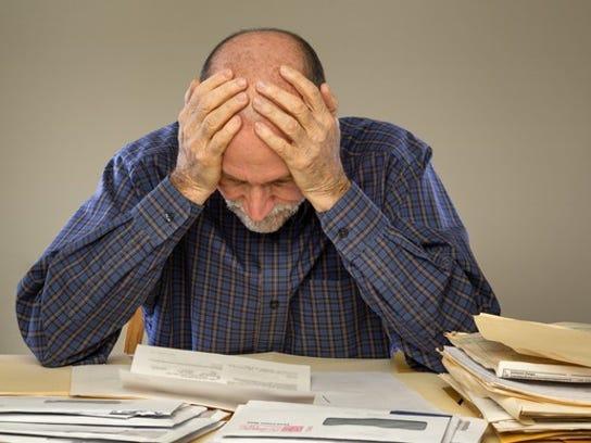 Frustrated man looking at bills.