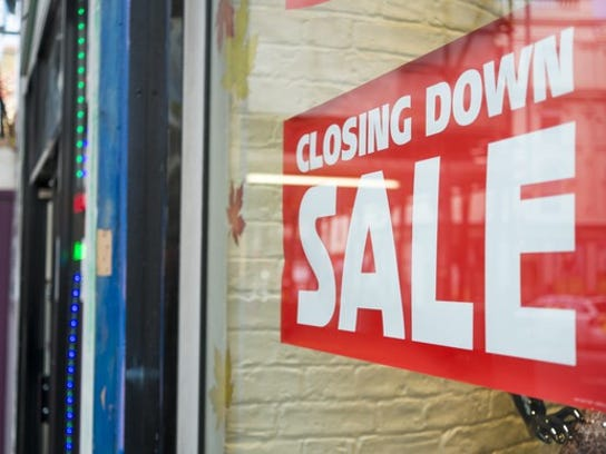 """Picture of a sign in a window that says """"closing down sale."""""""