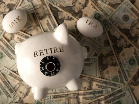 """Piggy bank with the word """"Retire"""" on it, sitting on a pile of cash. Also two eggs, one with '401k' written on it and the other with 'IRA' written on it."""