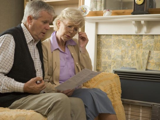 Senior couple, sitting on a sofa, reading a document.