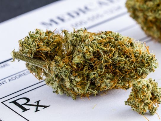 A cannabis bud atop a physician's prescription order.