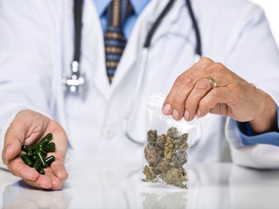 A doctor holding a bag of cannabis buds in one hand and cannabis-infused capsules in the other.