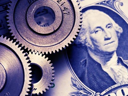 An assortment of gears sits atop a dollar bill.