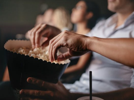 People eat popcorn at a movie theater