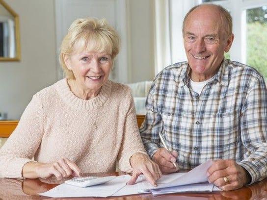 A smiling senior couple examining their finances.
