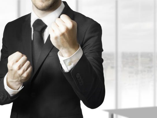 A man in a suit has his fists raised to fight.