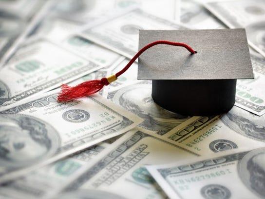 Graduation cap on a pile of $100 bills