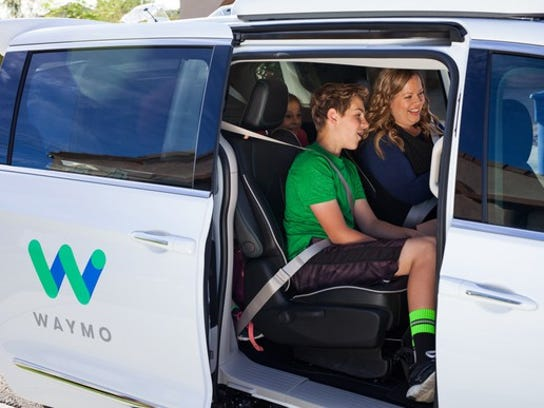 Several smiling riders in a Waymo equipped minivan.