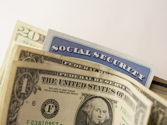 A Social Security card wedged in between cash bills.