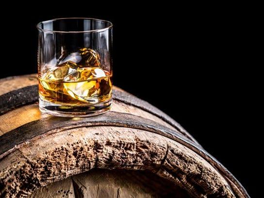 Glass of whiskey on an oak barrel.