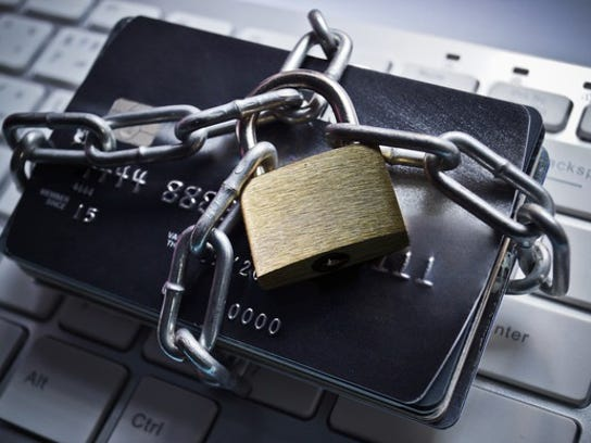 a bunch of credit cards tied up in a chain with a padlock, sitting atop a keyboard