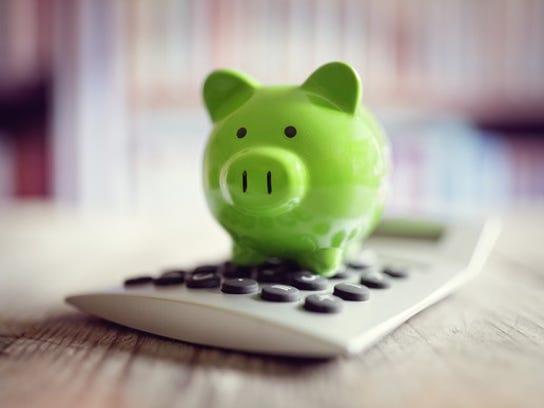 A green piggy bank sits atop a calculator.