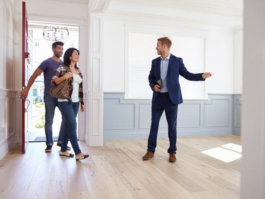 A man in business attire gestures to a couple walking into an empty house.