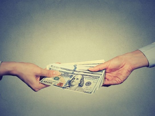 One person hands a stack of money to another.