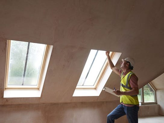 A home inspector in a yellow vest holds a clipboard as he looks at a window.