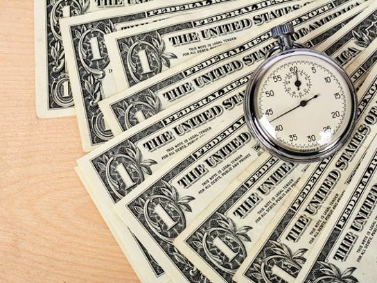 A stopwatch sits atop a pile of fanned-out dollar bills, signifying that time is money.