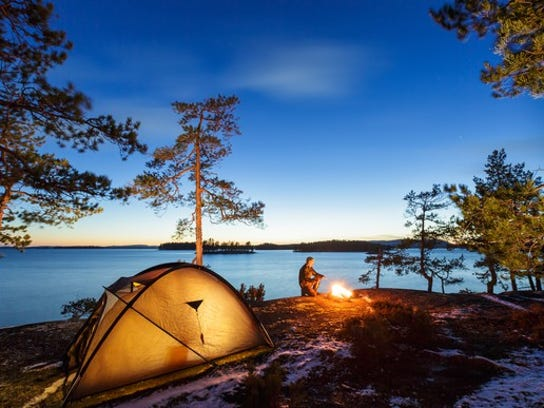A camping tent and a man by a campfire by a lake