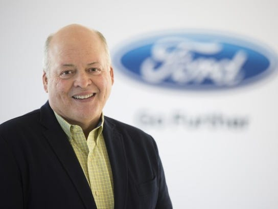 Jim Hackett in front of Ford's logo.