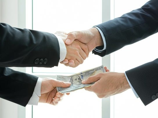 Two people shake hands while one hands money over to ther other.