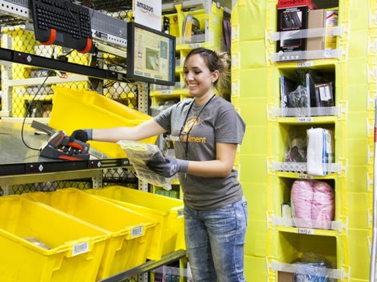 An Amazon employee sorting packages for shipment.