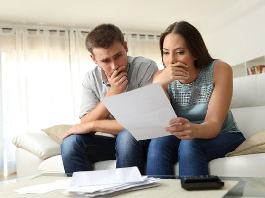 A young couple sitting on a couch and looking at a bank statement.