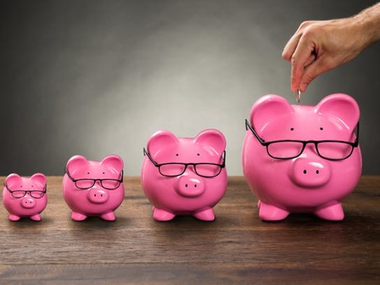 A series of progressively larger pink piggy banks wearing glasses, with a man's hand holding a coin over the largest one.