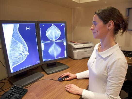 Technician looks at mammogram results on a computer