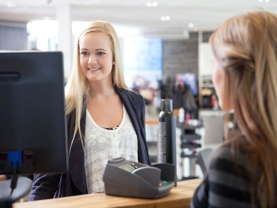 A female customer buys hair products from a smiling blond cashier