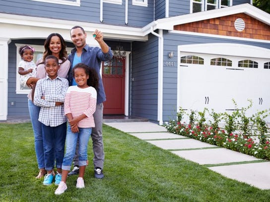 Family of five standing in front of new home