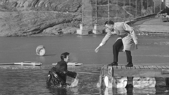 """Frank Sinatra, right, extends a hand to help Laurence Harvey from the lake at Central Park in New York during the filming of """"The Manchurian Candidate."""""""