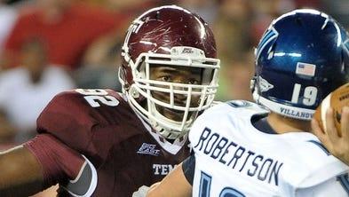 Temple Owls defensive lineman Shahid Paulhill, left, pressures Villanova quarterback John Robertson in 2012.