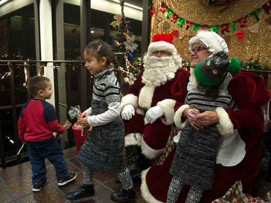 Evan Rodriguez, 3, left, looks back at Santa Claus as his sister, Flor Rodriguez, 8, walks away from hugging Santa Claus while their sister, Linsey Rodriguez, 4, gets a hug from Mrs. Claus during the Oxnard Police Department's Santa at the Station event Wednesday night.