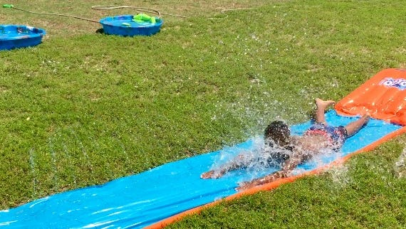 This July 23, 2016 photo shows a boy on a waterslide at the Salvation Army's Richard Hazel Youth Center near Salisbury. Despite sultry weather and three-digit temperatures, hundreds of schoolchildren and their families attended indoor and outdoor activities at the third annual Family Resource Fair sponsored by the Wicomico Early Childhood Council in partnership with the Wicomico County Board of Education and the Eastern Shore Parent Resource Alliance.