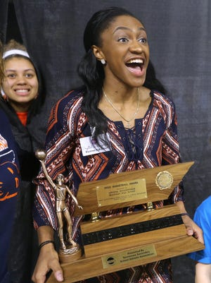 Blackman's Crystal Dangerfield reacts with her friends and teammates as she gets pictures taken after winning the 2016 Miss Basketball award for Class AAA, on Tuesday, March 8, 2016, at MTSU. Teammate Jada Hughes pokes her head through the curtain as they try to take pictures
