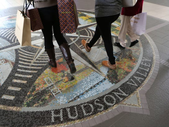 Shoppers pass over a Hudson Valley mosaic on the floor,